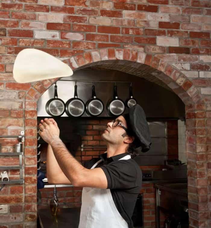 Pizzaiolo jonglant avec sa pâte