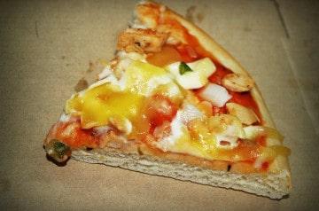 Un lugeur dévore une part de pizza en une seule bouchée