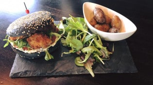 Cooking Pot - Burger : le merlan enchanteur , pain à l encre de sèche, merlan à la panure panko , cream cheese combawa citron vert et tomates confites, roquette . Servi avec pommes de terre grenailles
