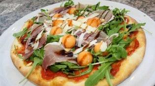 Pecorino - La pizza pecoriniens: Sauce tOmate, rOquette, prOsciuttO, pignOns de pin, billes de melon et velours de balsamique.